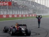 El piloto alemán de Fórmula Uno Sebastian Vettel de Red Bull Racing celebra junto a su coche de carreras el haber ganado el cuarto título consecutivo de Fórmula Uno en el Circuito Internacional de Buddh, en las afueras de Nueva Delhi. EFE