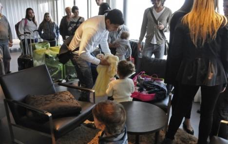 Sala VIP del aeropuerto: Suárez prepara a su hija previo a la salida a Europa tras los partidos con la selección. Coates y Cavani lo miran