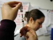 Los adultos solo se contagian de gripe un promedio de dos veces por década, según señaló un estudio médico, lo que sugiere que la mayoría de los estornudos y sensaciones de frío que obligan a millones de personas a pedir bajas laborales cada año se deben a otras bacterias. En la imagen, un enfermero prepara una vacuna contra la gripe durante una epidemia en una clínica de Boston, el 12 de enero de 2013. REUTERS/Brian Snyder