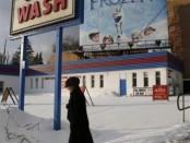 """El primer premio que la Academia del Cine concedió a una película animada fue un honor especial dado a Walt Disney en 1939 por la innovación en """"Blancanieves y los siete enanitos"""". La estrella infantil Shirley Temple entregó a Disney un Oscar de tamaño normal y siete miniaturas. El estudio fundado por el pionero de la animación, Walt Disney Animation Studios, nunca ha ganado un Oscar a la mejor película animada, una categoría creada en 2002. Esta previsto que esto cambie el domingo, ya que su éxito """"Frozen"""" es la favorita en una carrera tan diversa como la industria de la animación de Hollywood. En la imagen, una mujer avanza entre la nieve con un cartel de Frozen al fondo, en Toronto, el 26 de diciembre de 2013. REUTERS/Chris Helgren"""